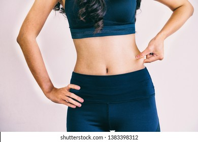 Young woman in sportswear touching her belly. Dieting and weight loss concept.
