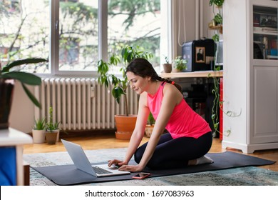 Young Woman in Sportswear Using Laptop,  Sitting on the Floor in her Living Room, Getting Ready for an Online Meeting or Workout Class