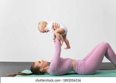Young woman in sportswear workout together with her baby. Happy mother laying on fitness mat with raised in arms son over her head. Concept of active lifestyle and motherhood