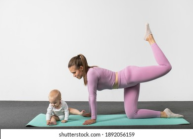 Young woman in sportswear workout together with her baby. Happy mother with son doing stretch yoga exercise. Concept of active lifestyle and motherhood