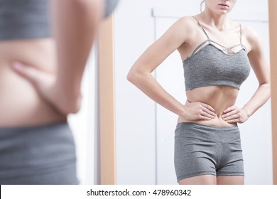 Young woman in sporty underwear looking at her refletion in the mirror