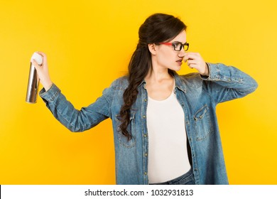Young woman with sprayer against unpleasant smell