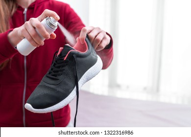 A young woman spraying deodorant on sweaty running shoes for eliminate unpleasant, bad smell. Shoe shine and care. Sport footwear needs in cleaning and odor removal. Copy space