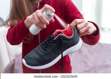 A young woman spraying deodorant on sweaty running shoes for eliminate unpleasant, bad smell. Shoe shine and care. Sport footwear needs in cleaning and odor removal.