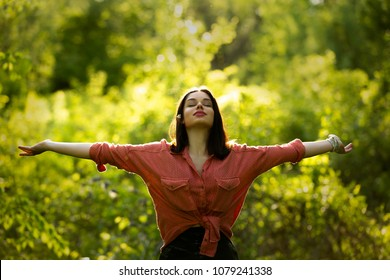 Young woman spreading arms to the sky. Outdoor summer day. Meditation and freedom concept