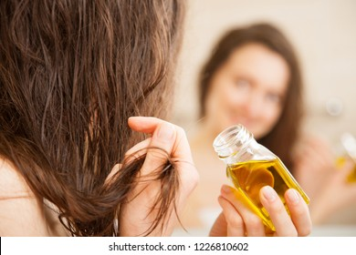 Young woman spreading oil mask over her hair in front of a mirror