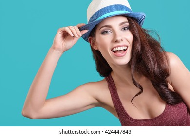 Young Woman with spring hat against blue background
