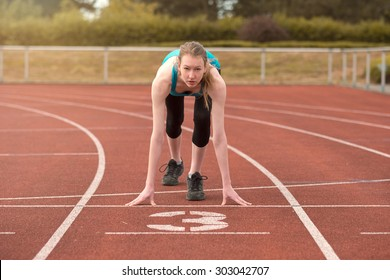 Young woman sprinter in the starter position on a race track at a sports stadium looking up at the camera with determination