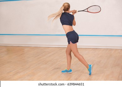 Young woman squash player exercise game in the gym