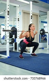 Young woman squats with a barbell in the gym.