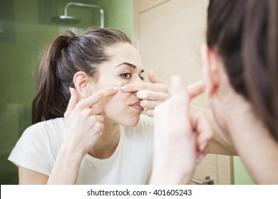 Young woman squeeze her acne in front of the mirror. Skin problems,woman hiving pimple