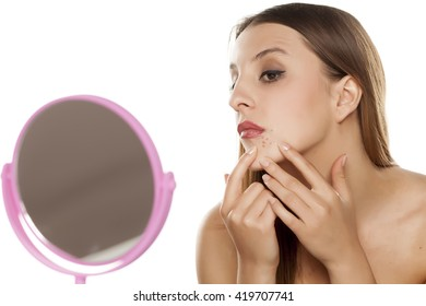 young woman squeezing a pimple in front of the mirror