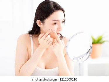young woman squeezing pimples in front of mirror