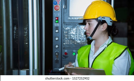 Young woman staff writing on clipboard while check machine. factory and SME concept .