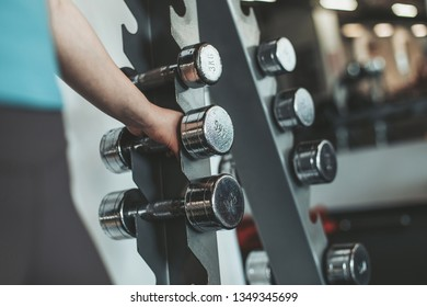 Young woman stand in gym room. Cut view caucasian european model in sportswear holding dumbbell with hand.