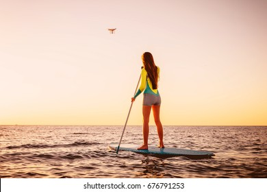 Young woman Stand Up Paddle Surfing and drone copter with beautiful sunset colors