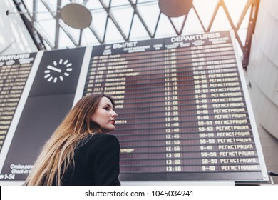 Young woman standing against flight scoreboard in airport