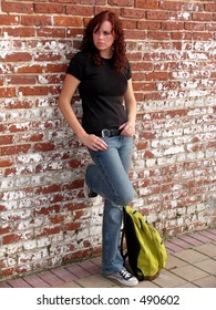 Young woman standing against wall with bookbag