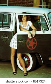 Young Woman standing in alley next to old van.