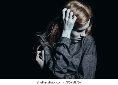 Young woman standing alone in a dark room at night trying to shake off a nightmare