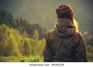 Young Woman standing alone outdoor with wild forest mountains on background Travel Lifestyle and survival concept rear view