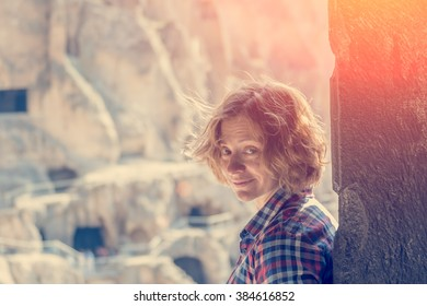 Young woman standing in arched door in a cave city