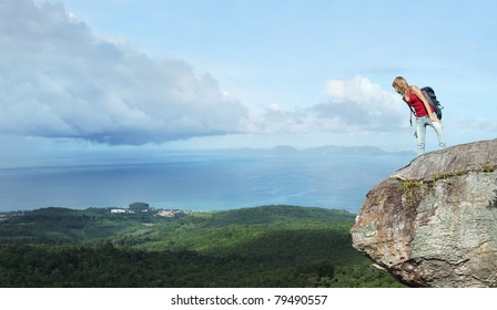 Young woman standing with backpack on cliff's edge and looking down to a valley
