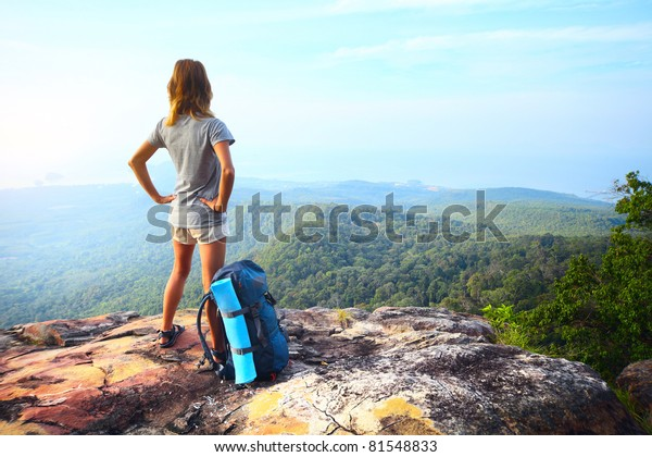 Young woman standing with backpack on cliff's edge and looking into a wide valley