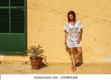 Young woman standing in a beach dress and bikini standing in front of a yellow wall