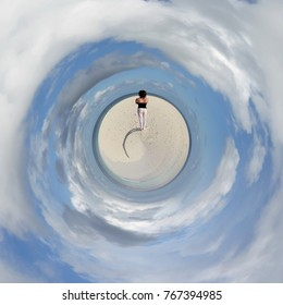 A young woman standing at the beach of a Maldivian island from a tiny world perspective