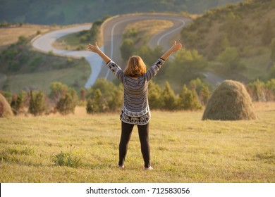 Young woman standing in a beautiful open field on mountain with her arms raised up in the air, feeling confident. Success and freedom concept.