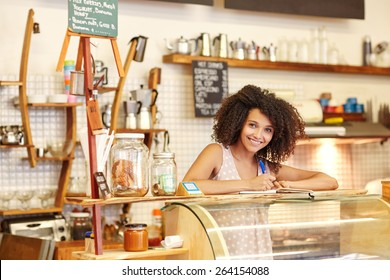 A young woman standing behind the counter in a coffee shop