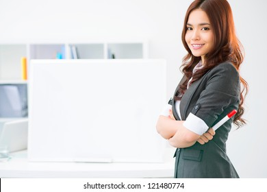 Young woman standing at a blank whiteboard
