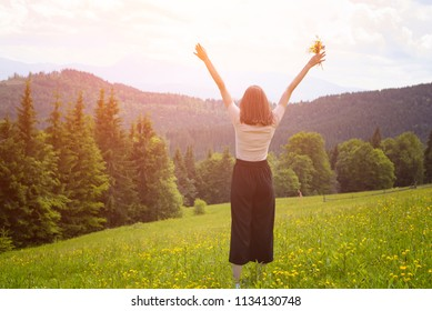Young woman standing with a bouquet of flowers and hands raised. Forest and mountains in the background. Back view