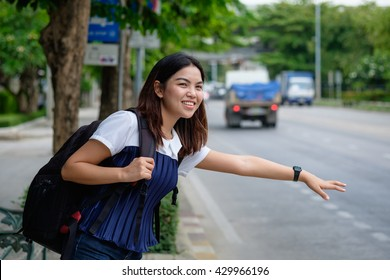 Young woman standing at bus stop on street of city. Asian student girl waiting  bus in private dress at Public transport  in Thailand