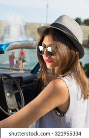 Young woman standing by car,beautiful bright sunny summer day. Summer vacation car road trip freedom concept.Teenage hipster girl wearing hat,sunglasses and fashionable dress.Smiling,positive.