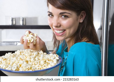 Young woman standing by fridge with bowl of popcorn, smiling, portrait, close-up