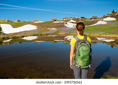Young woman standing by the lake enjoying the view of the huts and crocuses on Velika Planina / Big Pasture Plateau in Slovenia.