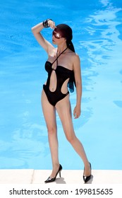Young woman standing by pool