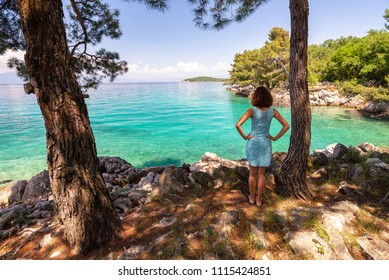 Young woman is standing by the sea under the trees in a beautiful dress near Malinska, Croatia
