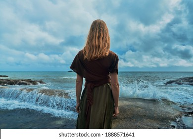 A young woman is standing by the sea watching the waves break