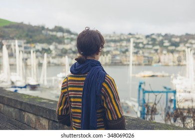 A young woman is standing by a stone wall in a village and is looking at the boats moored in the estuary