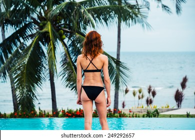 A young woman is standing by a swimming pool with palm trees and the ocean in the background
