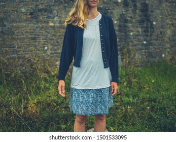 A young woman is standing by a wall in the countryside
