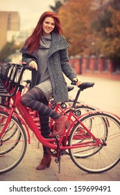 Young woman standing at city bike.