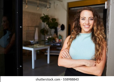 Young woman standing in clothes shop doorway, arms crossed