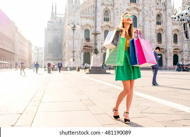 Young woman standing with colorful shopping bags on the main square in front of the famous duomo cathedral in Milan. Happy shopping weekend in Milan