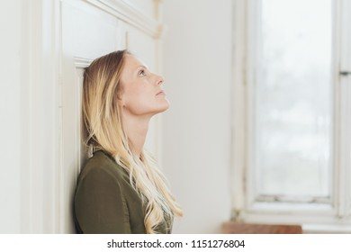 Young woman standing daydreaming indoors leaning against a white wooden door looking up with a faraway expression
