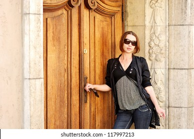 Young woman standing at the entrance door