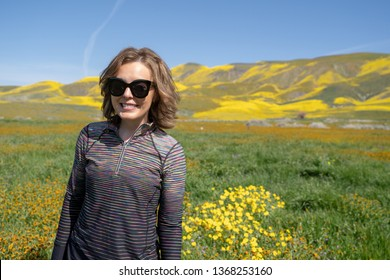 Young woman standing in a field poses during the super bloom at Carrizo Plain National Monument in California. Wearing sunglasses and athleisure clothing